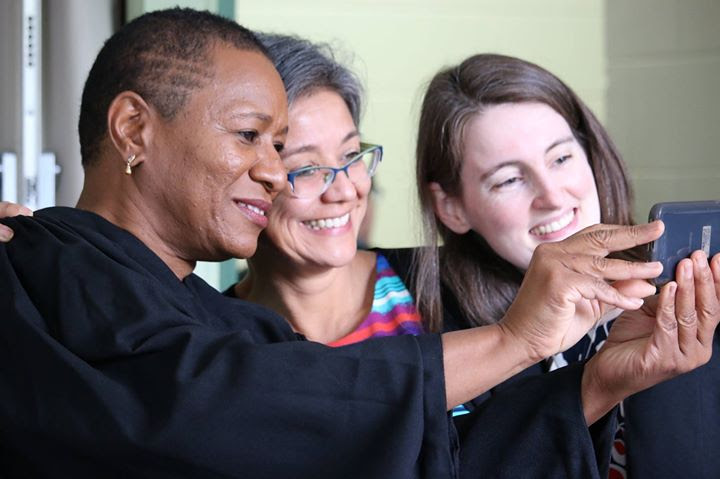 Three women in black graduation robes pose for a selfie: one woman is black, one woman is latina, one woman is white