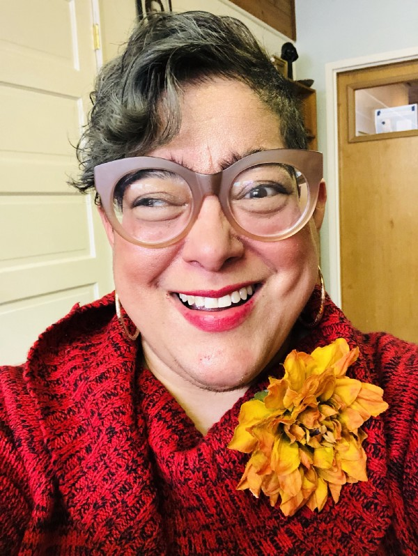 Latinx person smiling, wearing big glasses, a red sweater, and a yellow flower